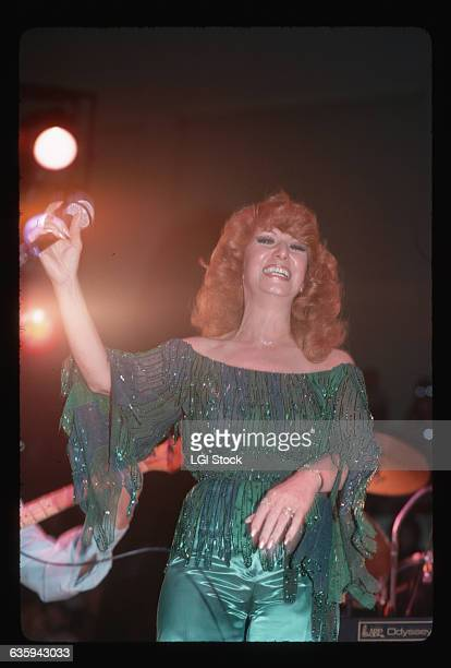 1978Country/western singer Dottie West is shown on stage smiling and holding a microphone