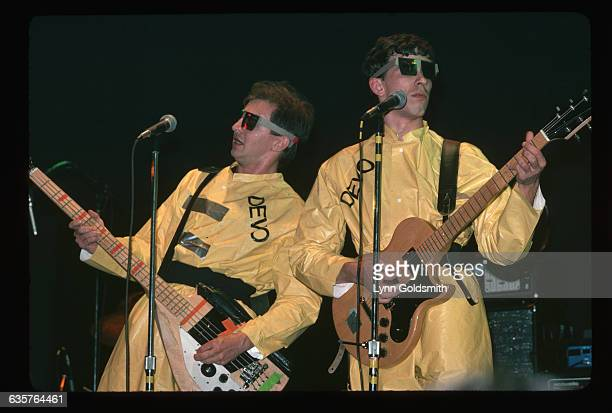 1978Two unidentified members of the band Devo are shown on stage playing their guitars in concert They wear yellow jumpsuits with Devo imprinted on...