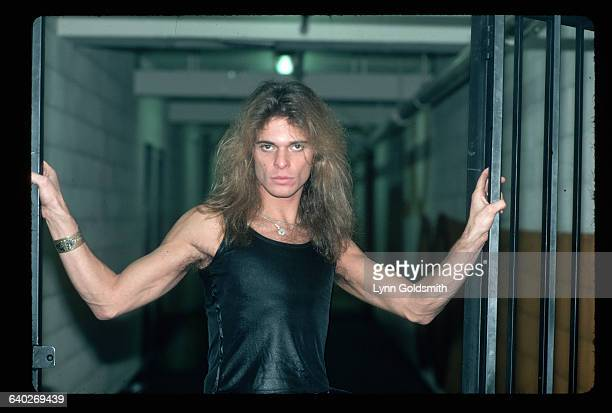 David Lee Roth singer with the rock and roll group Van Halen is shown standing between two gates in this waistup photograph