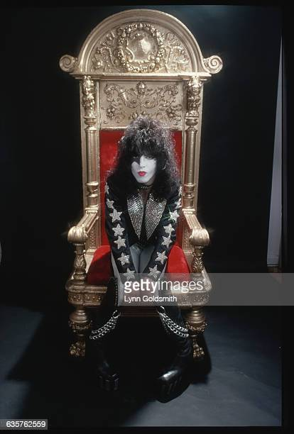 Paul Stanley, lead singer of the group KISS, is shown seated in a throne n this studio portrait.