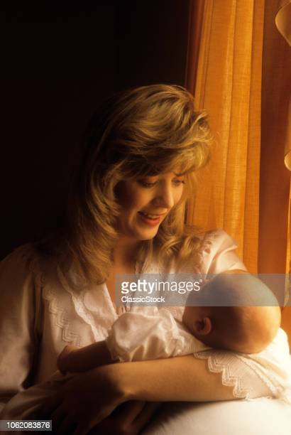 1980s 1990s WOMAN HOLDING SLEEPING BABY DAUGHTER