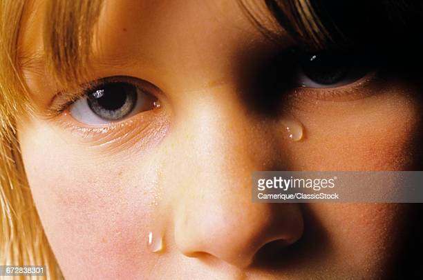 1980s CLOSEUP FACE CRYING TEEN GIRL WITH TEARS ON HER CHEEK LOOKING AT CAMERA