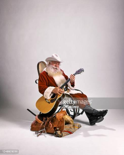1980s Cowboy Santa Claus Looking At Camera Sitting In Bentwood Rocker Beside Western Saddle Playing Guitar Wearing White Hat