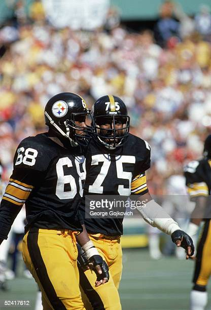 Defensive end LC Greenwood and defensive tackle Mean Joe Greene of the Pittsburgh Steelers walk on the field during a circa 1980 NFL game at Three...