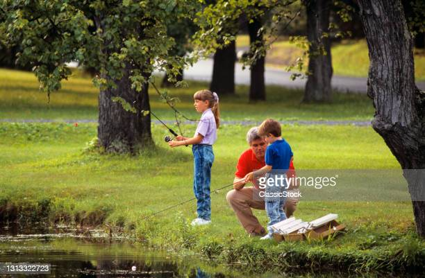 1980s Father With Son And Daughter Fishing.