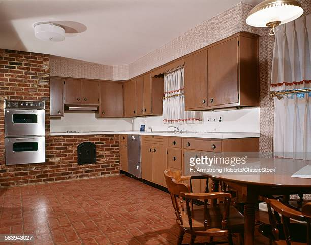 1980s KITCHEN WITH DARK WOODEN CABINETS BRICK WALL AND STAINLESS STEEL DOUBLE OVEN