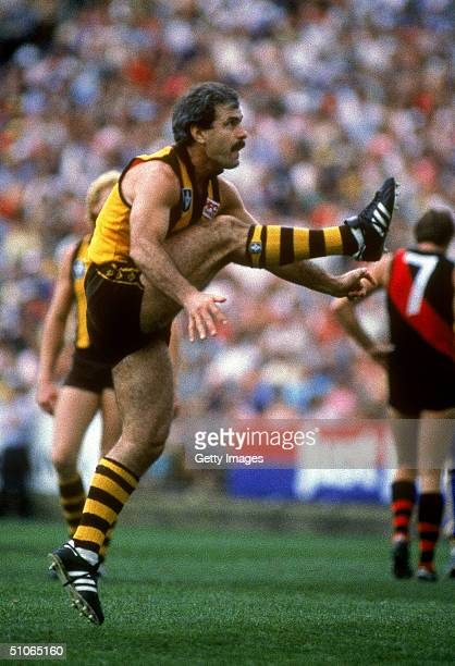 1980s: Leigh Matthews of the Hawks kicks for goal during a VFL match between the Hawthorn Hawks and the Essendon Bombers held at the Melbourne...