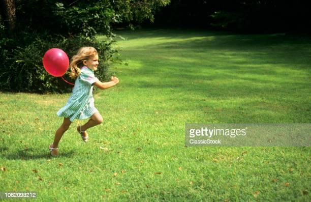 1980s LITTLE GIRL WITH A RED BALLOON RUNNING IN THE GRASS