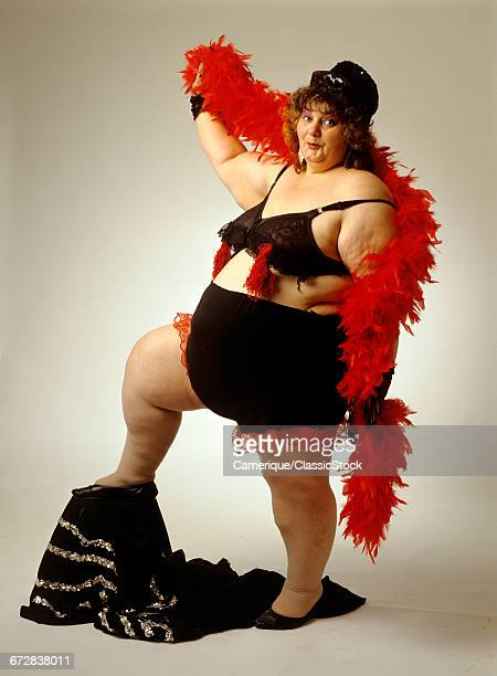 1980s OBESE WOMAN WEARING SEXY LACY RED AND BLACK UNDERWEAR AND RED FEATHER BOA LOOKING AT CAMERA