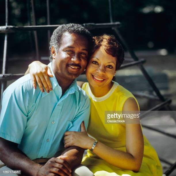 1980s Portrait Smiling African American Couple Sitting Side by Side Hugging Looking At Camera Man Blue Shirt Woman Yellow Dress