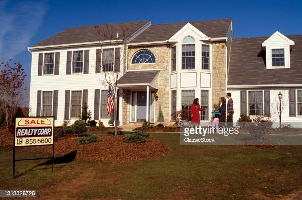 1980s Realtor Showing Family Outside Of House For Sale.