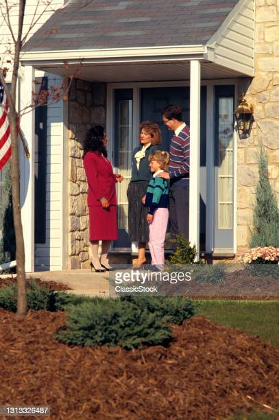 1980s Realtor Talking To Family Outside Of House For Sale.