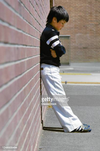 1980s Sad Depressed Angry Solitary Young Boy Standing Leaning Against Brick Wall In School Playground