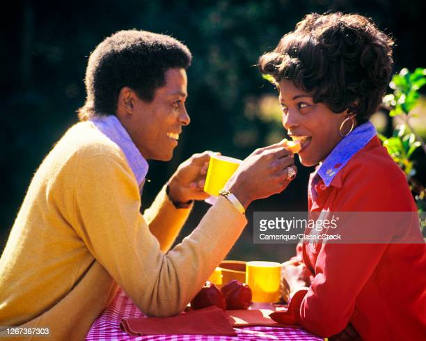 1980s Smiling AfricanAmerican Couple Husband And Wife Eating Sharing Breakfast Meal Food Together Outdoors In Bright Sunlight