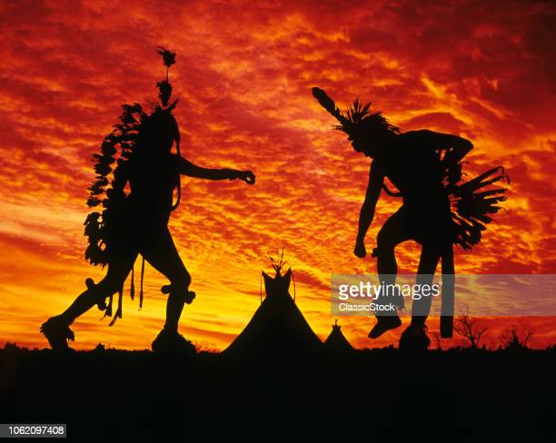 1980s SUNRISE OR SUNSET SILHOUETTE OF TWO NATIVE AMERICAN INDIAN MEN DANCING AT POW WOW WITH TEPEES IN BACKGROUND