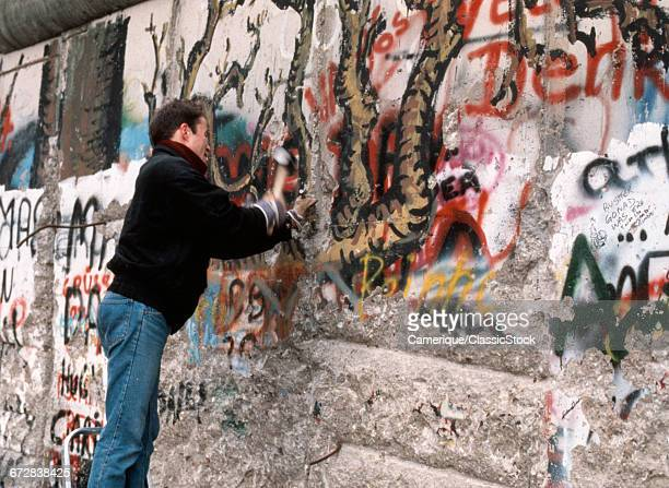 1980s TEENAGE BOY CHIPPING AWAY AT THE GRAFFITI SPRAY PAINTED BERLIN WALL WITH HAMMER AND CHISEL NOVEMBER 1989