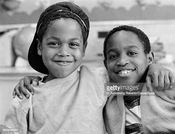 1980s TWO AFRICAN AMERICAN BOYS SMILING EMBRACING SHOULDER TO SHOULDER ONE BOY HAS CAP ON BACKWARDS OUTSIDE LOOKING AT CAMERA