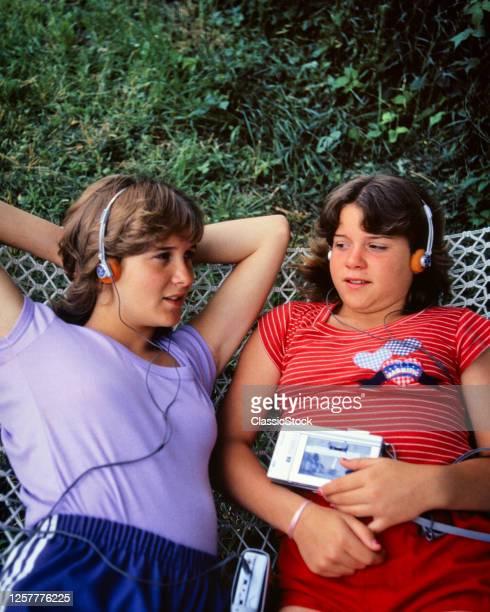 1980s Two Teen Girls Lying On Hammock Listening Foam Headphones To Sounds Music Recorded Cassette On Portable Media Player
