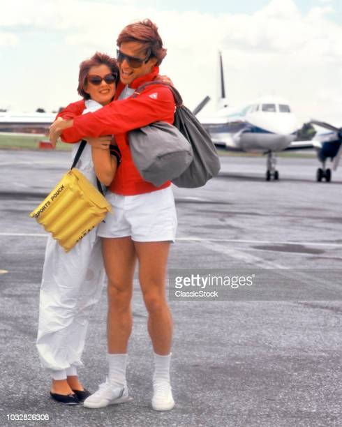 1980s UPSCALE COUPLE ON TARMAC PRIVATE PLANE WEARING SPORTY TENNIS CLOTHES HUGGING
