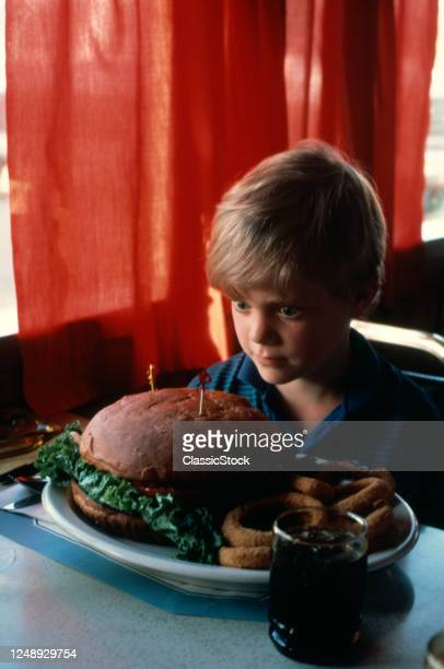 1980s Wide-Eyed Bug-Eyed Boy Overwhelmed Confronted With Giant Hamburger Diner Meal