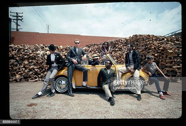1980The skarevival band Selecter is shown posed in front of and around a yellow VW Bug convertible They are all in front of a pile of logs