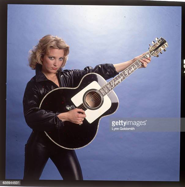 1981Tanya Tucker is shown in a studio portrait holding a black guitar She wears a black shirt and black leather pants