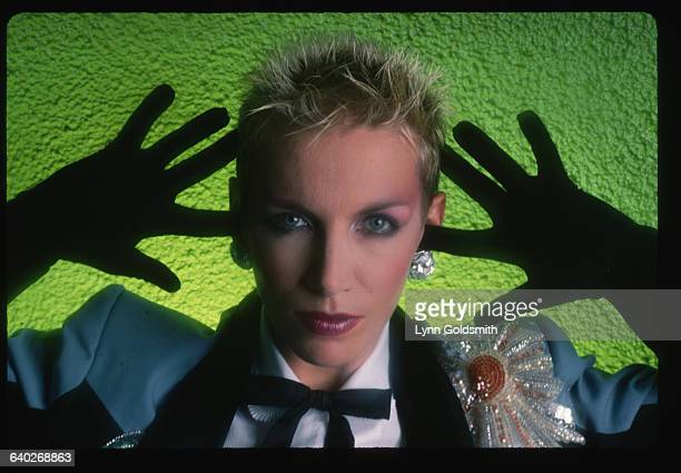 1987Annie Lennox of the Eurythmics is shown in a blue jacket with black gloves in front of a green background in this studio portrait