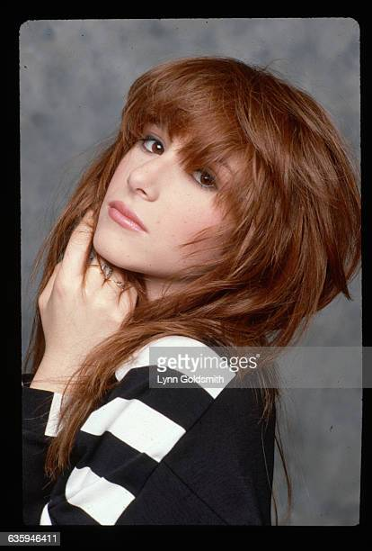 1987Pop singer Tiffany is shown in a head and shoulders closeup studio portrait her head on her hands She wears a black and white shirt