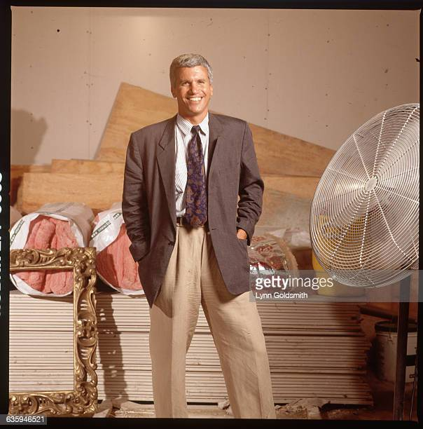 Art dealer Larry Gagosian is shown standing in front of construction materials and a gold picture frame.