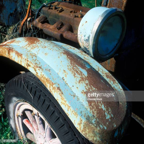 1990s Abandoned Antique Automobile Rusty Metal Fender Wood Spoke Wheel Rubber Tire Brass Headlight And Iron Engine Block.