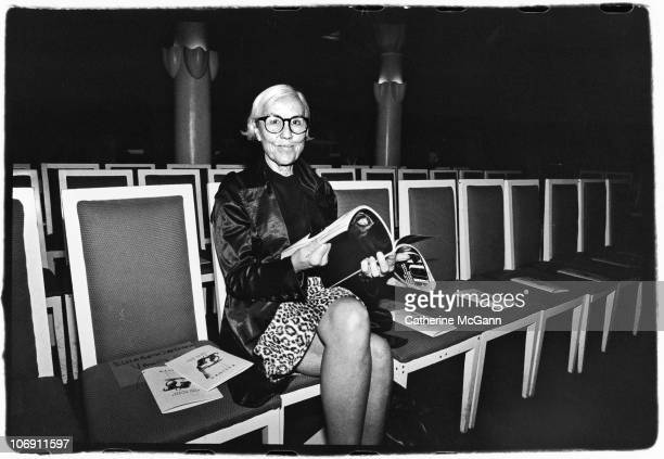 American fashion editior Polly Mellen poses for a photo while reading Vogue magazine in the front row of a Kalinka fashion show in the 1990s in New...