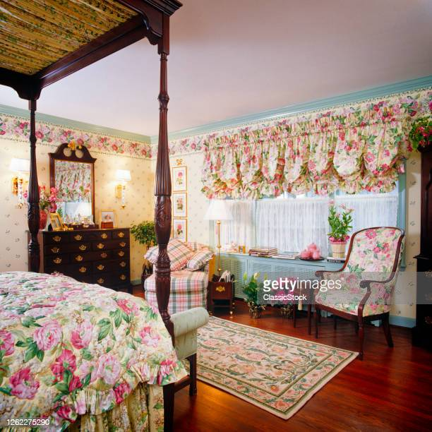 1990s Bedroom Interior Floral Chintz Fabric On Bedspread Wallpaper Border And Curtains Four Poster Canopy Bed Bureau Mirror