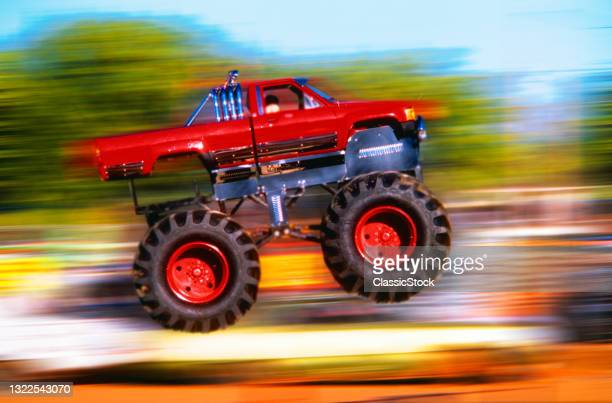 1990s Big Wheeled Red Modified Pickup Truck Jumping Blurred Background.