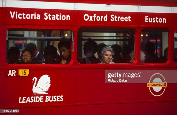 1990s commuters stare out the window of their red London Routemaster bus operated by Leaside Buses on 19th June 1994 The bus is a traditional design...