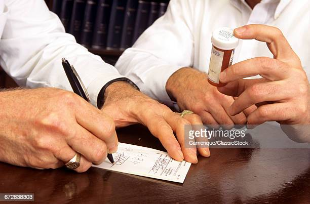 1990s DOCTOR WRITING REFILL PRESCRIPTION FOR PATIENT HOLDING PILL BOTTLE