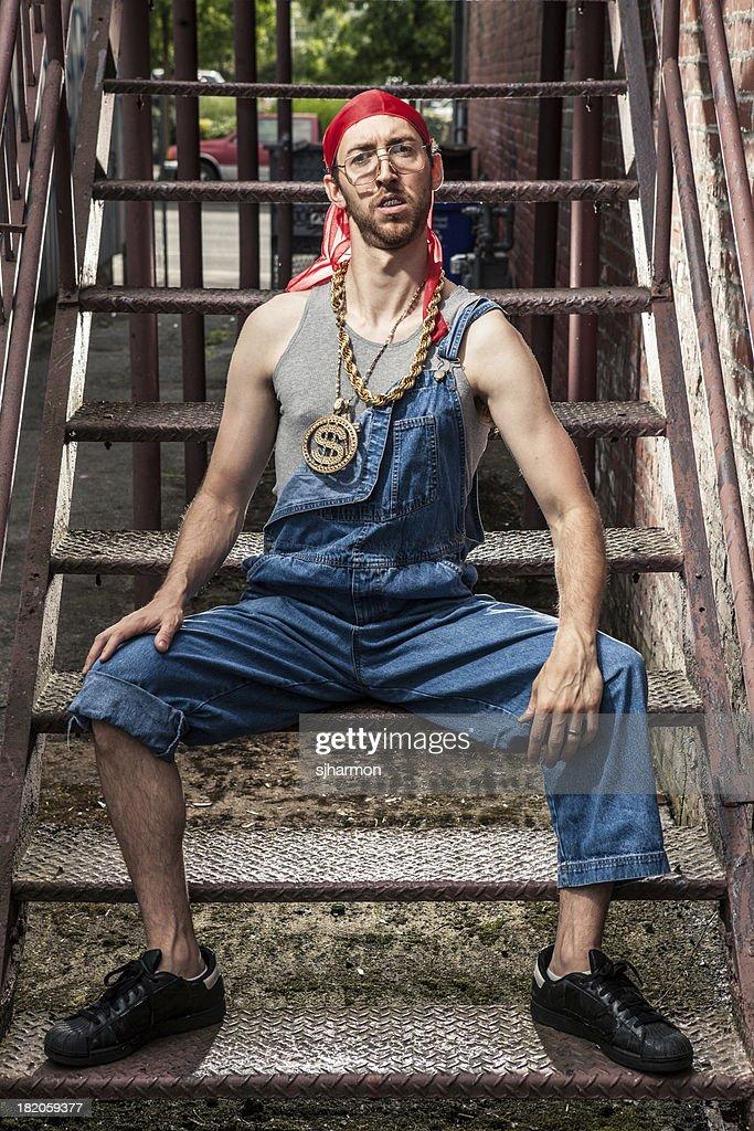 Noventa Hip-Hop payasear Nerd Guy con Bling en la oscuridad Alley : Foto de stock
