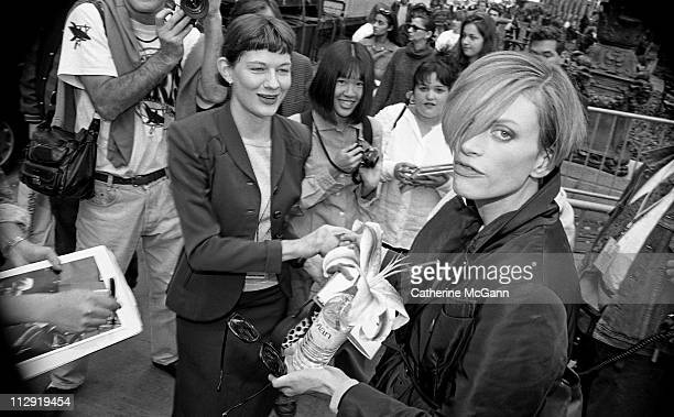 Kristen McMenamy holds a flower while a fan asks for an autograph during fashion week in the mid 1990s in New York City New York