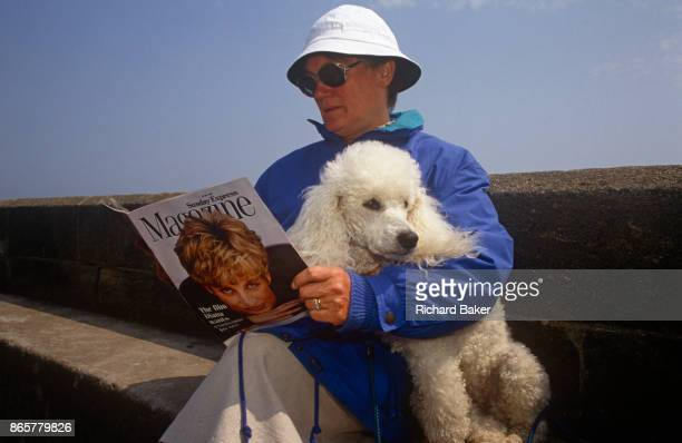 A 1990s lady sits with her pet poodle on a sea wall reading the Sunday Express magazine that features Princess of Wales on the cover on 19th July...