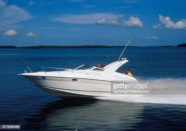 1990s MOTOR BOAT SPEEDING ACROSS THE WATER WITH FOUR PASSENGERS
