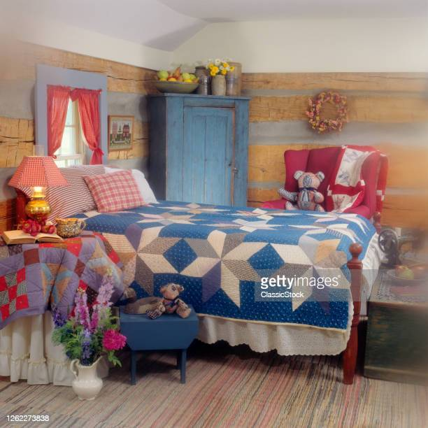 1990s Rural Americana Theme Guest Bedroom In Log Cabin Bed With Quilt And Textile Pillows And Vase Of Flowers On Floor