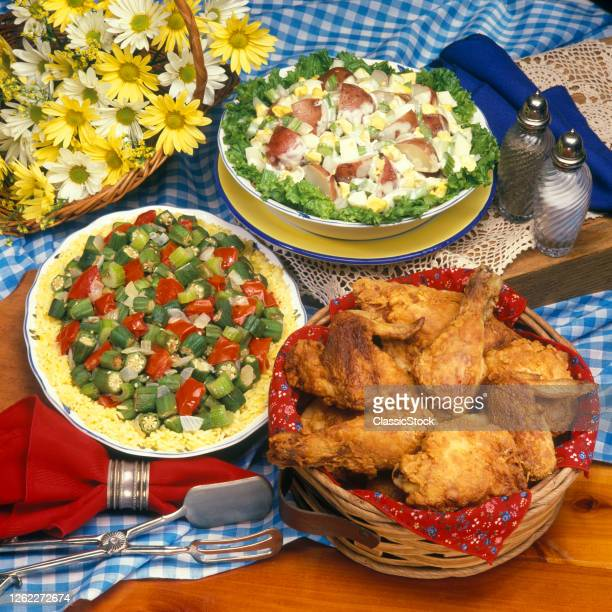 1990s Traditional Picnic Style Fried Chicken With Okra Salad And Potato Salad Beside A Basket Of Yellow And White Daisy Flowers