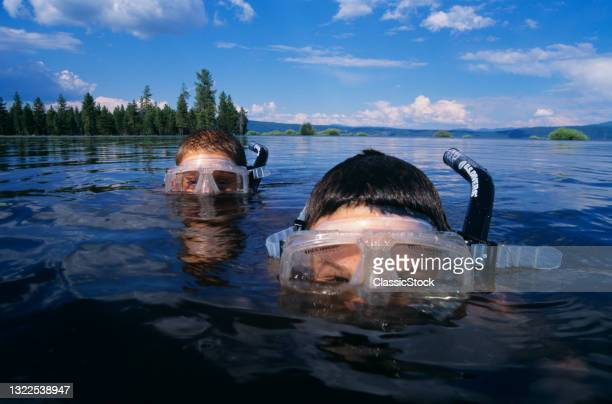 1990s Two Boys Snorkeling In Mountain Lake Peering Over Water Looking At Camera.