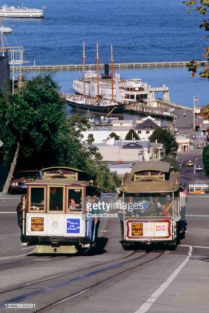 1990s Two Cable Cars On Hyde Street San Francisco Maritime National Historical Park In Distance San Francisco California USA.