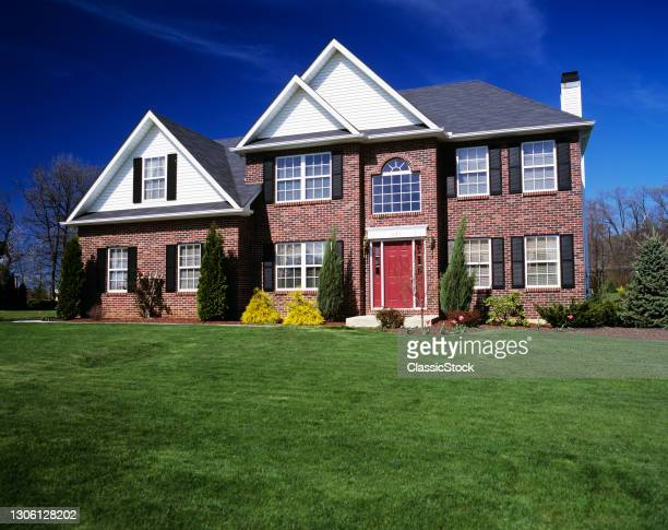 1990s Two-story Brick House With Landscaped Lawn And Red Front Door.