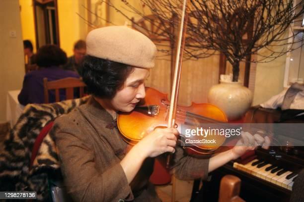 1990s Woman Playing Violin In Restaurant Hanoi Vietnam.