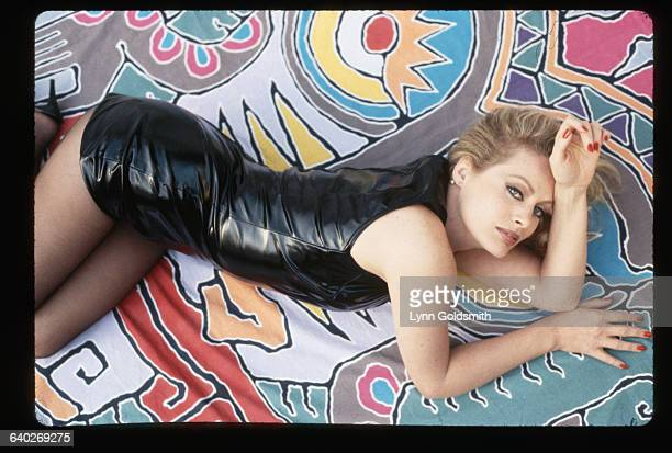1991Photo shows actress Beverly D'Angelo wearing a black leather dress lying on a colorful sheet