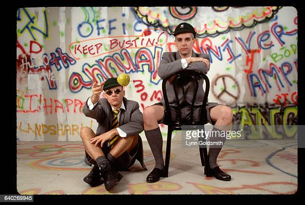 1991Pop/dance group The Pet Shop Boys are shown seated in front aof a white wall with graffiti on it They wear schoolboy jackets shorts and hats