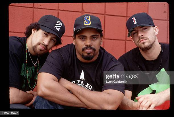 1992Left to right BReal Sen Dog and DJ Muggs of the group Cypress Hill are shown seated in front of a red wall All three wear baseball caps and...