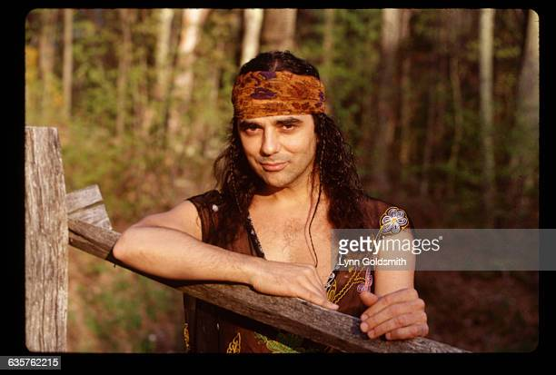 1993Producer and musician Daniel Lanois is shown outdoors leaning on a wooden fence He wears a bandana and a vest over his shirtless torso