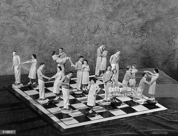 Nine couples in various poses on a chessboard while a single human chess figure looks hopefully off the board to the right